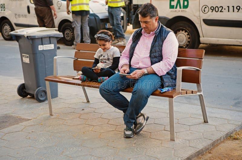 Barcelona, Espanha - 30 de mar?o de 2016: O homem e a menina do pai procuram nos smartphones que sentam-se no banco na rua da cid imagens de stock royalty free