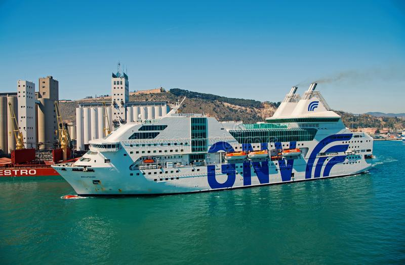Barcelona, Espanha - 30 de mar?o de 2016: raps?dia Genebra do navio ou do forro GNV no porto do mar na paisagem da montanha Coste fotos de stock