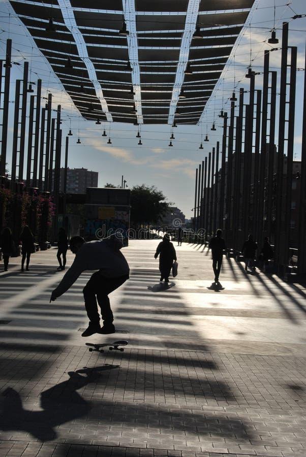 BARCELONA, ESPANHA - EM DEZEMBRO DE 2017: Menino retroiluminado que patina em um streer sob parasóis em uma manhã quieta do inver imagens de stock royalty free
