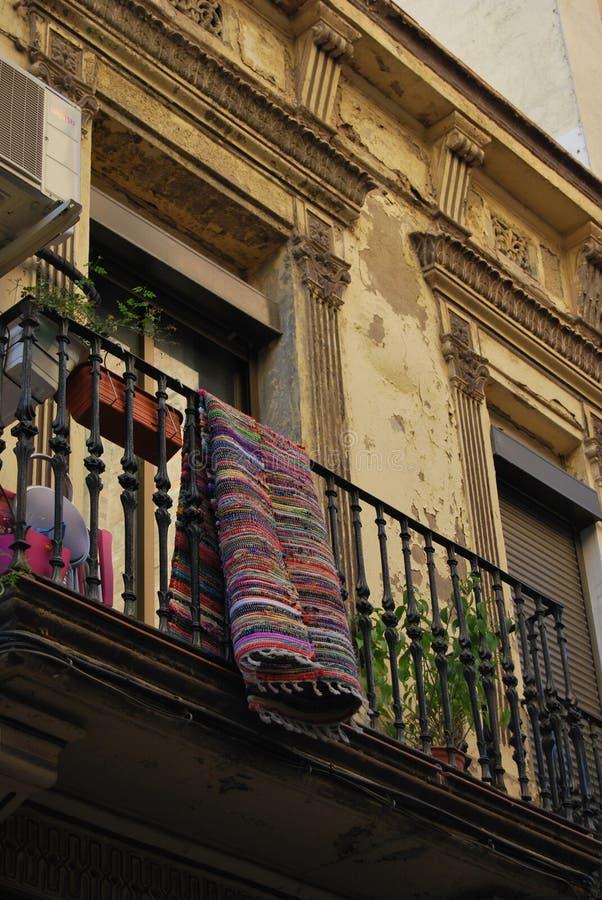 BARCELONA, ESPANHA - EM DEZEMBRO DE 2017: Tapete colorido que pendura de um balcão velho imagem de stock