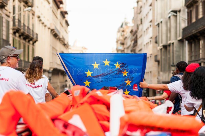 Barcelona, Hiszpania 17 2019 Lipiec: otwarci ręka aktywiści maszerują mienia dinghy gumową łódź z lifebelts jako symbol śródziemn obrazy stock