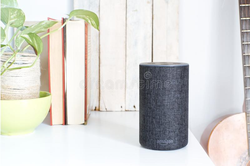 BARCELONA, JULY 1, 2019: Alexa Echo smart loudspeaker next a Spanish guitar and some books in a livingroom. stock image