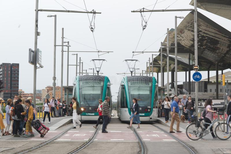 BARCELONA JUNE 14, 2019: Two tram trains on the rails and a crowd next to the tramway station in Barcelona stock photography