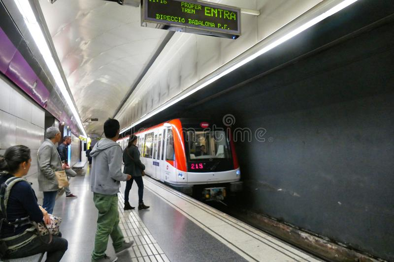Barcelona metro station tunnel with people seated and standing waiting train stop sign in fore royalty free stock photography