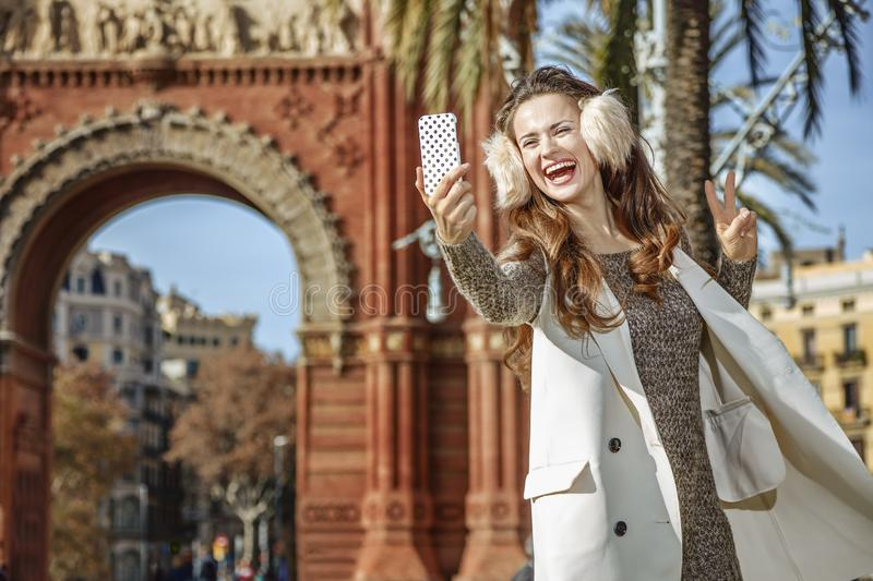 Fashion-monger taking selfie and showing victory gesture. In Barcelona for a perfect winter. Portrait of smiling elegant fashion-monger in earmuffs in Barcelona stock photo