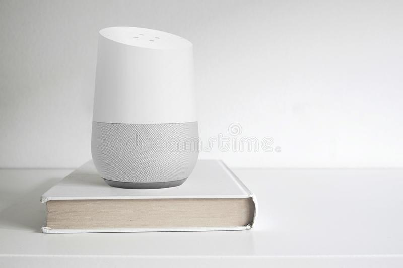 BARCELONA - SEPTEMBER 2018: Google Home smart speaker on a book on a shelf stock image