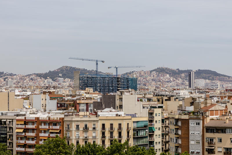 Barcelona skyline with constructing site. Barcelona city skyline with construction site blue cranes overtop the roofs royalty free stock photography