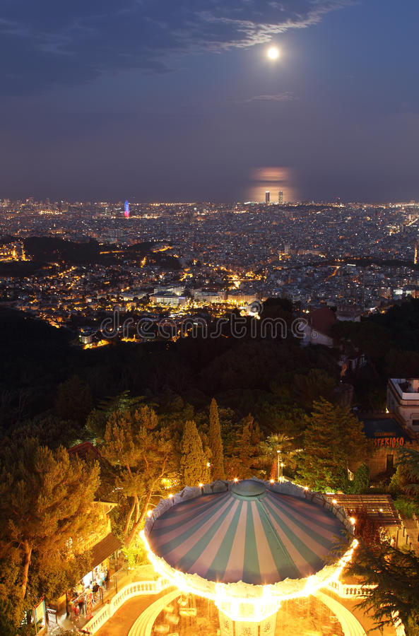 Barcelona skyline at night. With Tibidabo carousel at foreground and super moon at background royalty free stock photos