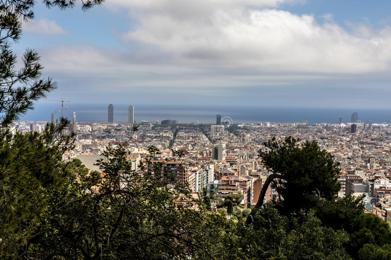 Barcelona skyline with sea from park Güell. Barcelona skyline with sea and Sagrada Familia clouds and trees from park Güell stock images