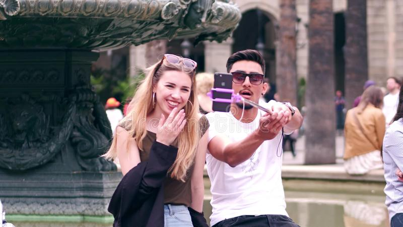 BARCELONA, SPAIN - APRIL, 16, 2017. Beautiful interracial young couple making selfies with a mobile phone and a rod near stock photo