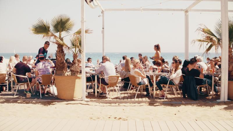 BARCELONA, SPAIN - APRIL, 15, 2017. Long steadicam shot of people in crowded beach restaurant royalty free stock image
