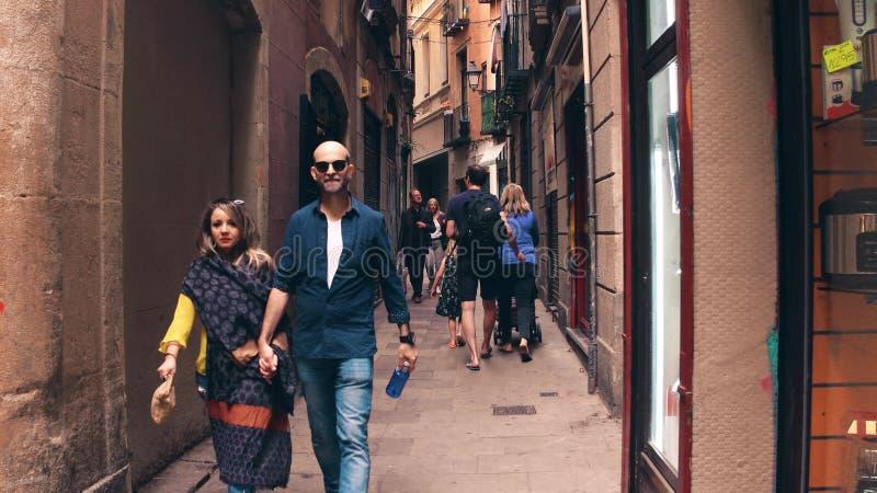 BARCELONA, SPAIN - APRIL, 15, 2017. Tourists walk along narrow pedestrian old town street. BARCELONA, SPAIN - APRIL, 15, 2017 Tourists walk along narrow royalty free stock images