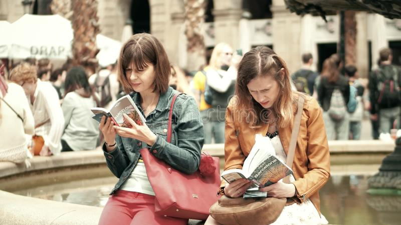 BARCELONA, SPAIN - APRIL, 16, 2017. Two young women reading city tourist guide books near the fountain royalty free stock image