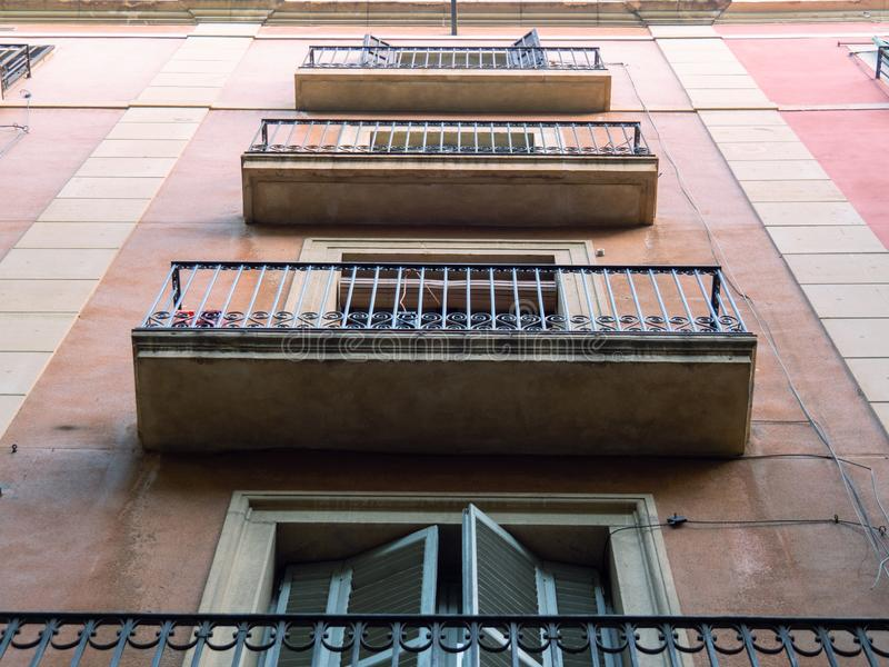 Barcelona, Spain - august 2019: pink building in city center, middle view. Balconies with black curved railing, bottom. Up view. Selective soft focus. Blurred stock photo