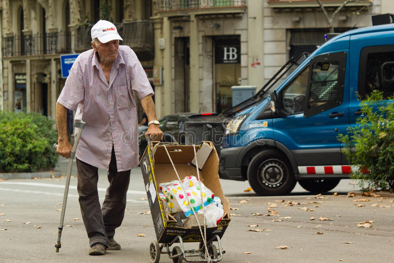 Barcelona, Spain, 16 august 2016: poor lean old man with trolley walk on street. With police van behind him in Eixample district stock images