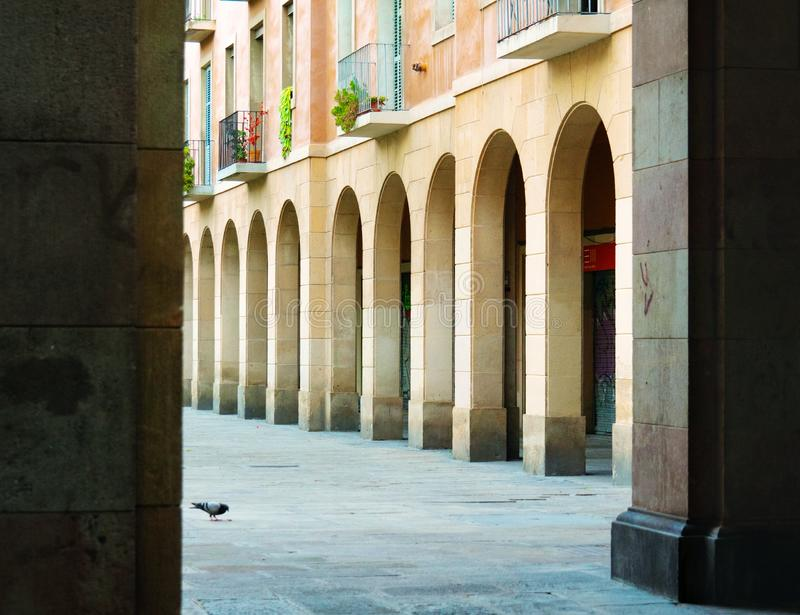 Barcelona, Spain - august 2019: vintage beige building with arches and columns in the center of Barcelona, middle view. Dove near building with balconies stock photos