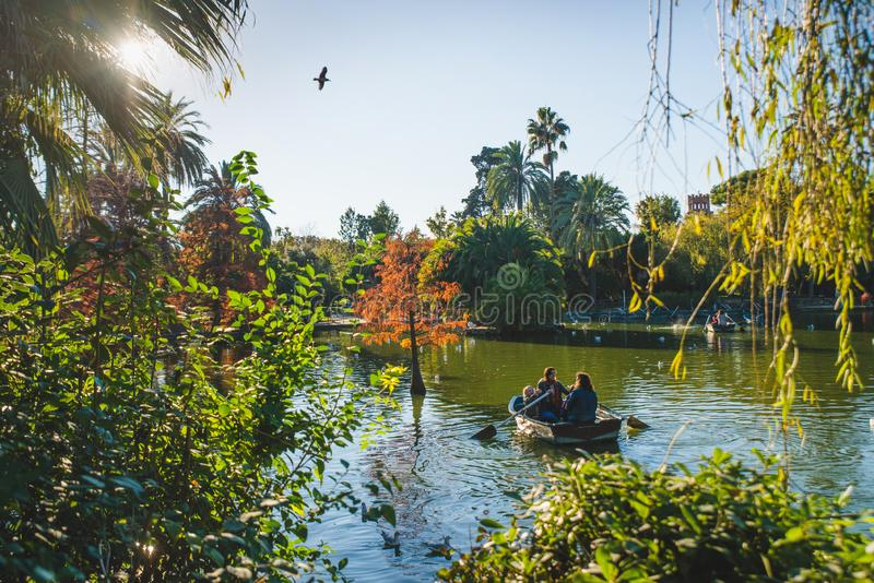 Barcelona, Spain - 24.11.2018: Beautiful day in Ciutadella Park, view of green trees and a boat with people in a small lake from royalty free stock images