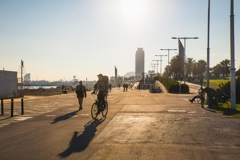 Barcelona, Spain - 05.12.2018: Beautiful sunny day with people cycling. And walking along a street close to the beach royalty free stock images