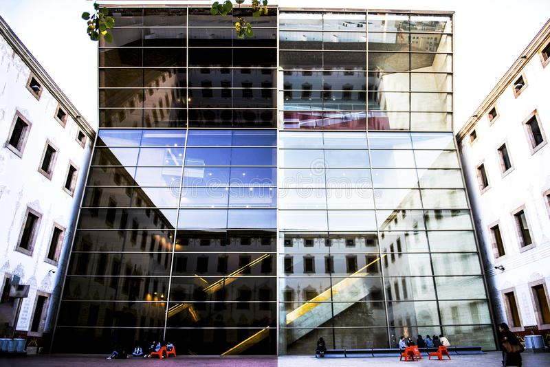 Barcelona Spain, building with mirrored glass. Square, people stock photo