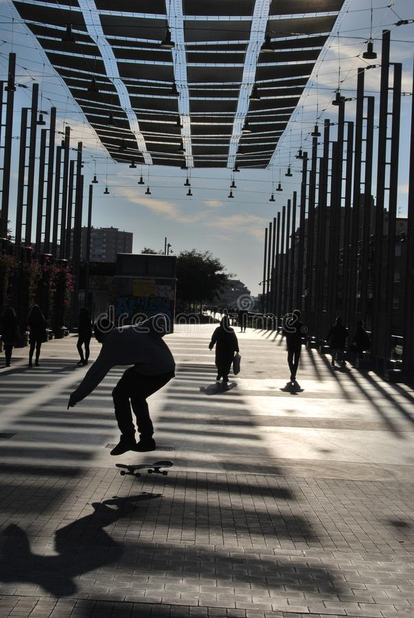 BARCELONA, SPAIN - DECEMBER 2017: Backlit boy skating in a streer under parasols in a quiet winter morning. royalty free stock images