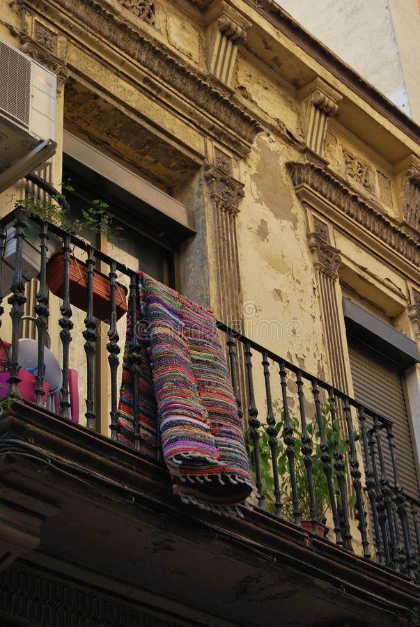 BARCELONA, SPAIN - DECEMBER 2017: Colorful carpet hanging from an old balcony stock image