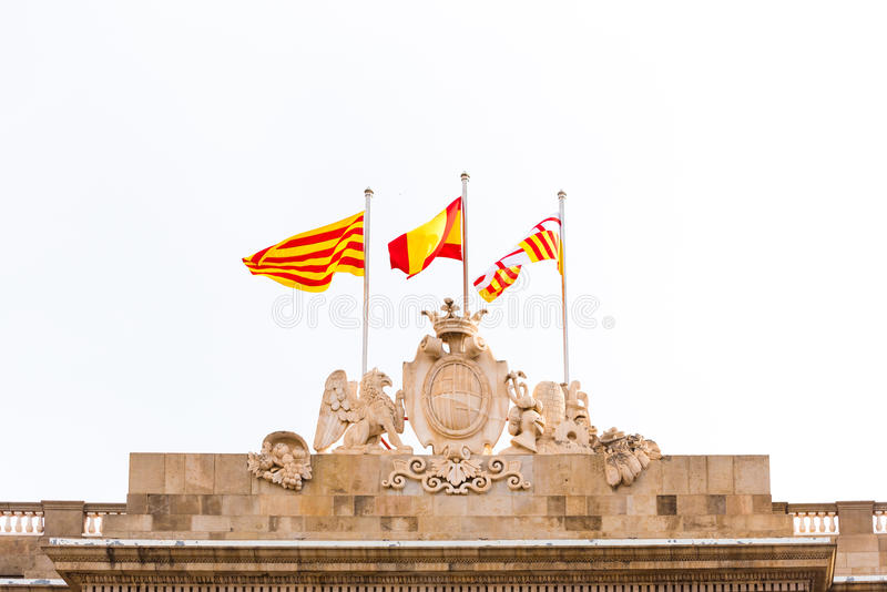 BARCELONA, SPAIN - FEBRUARY 16, 2017: City Council Building. Coat of arms and flags of Spain. Copy space for text. Isolated on white background stock photo