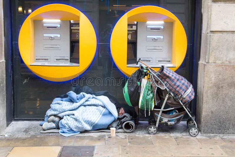 BARCELONA, SPAIN, February 4, 2018 Homeless man covered with blankets sleeping under ATMs, near him stands a stroller with his st royalty free stock image