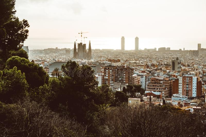 View of Barcelona on a cloudy day with a layer of air pollution. Photo taken from Park Guell: cityscape, skyline. BARCELONA, SPAIN - February 2019: View of royalty free stock image