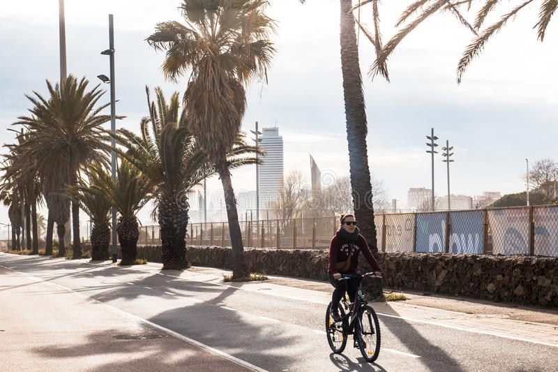 BARCELONA, SPAIN, February 6, 2018 Young girl in black sunglasses rides a Bicycle on an asphalt Bicycle path on the background royalty free stock image