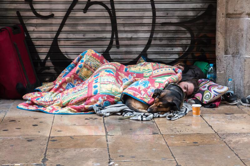 BARCELONA, SPAIN, February 4, 2018 A young guy, a girl and a dog. Covered with blankets sleeping on the street in the rain stock photo