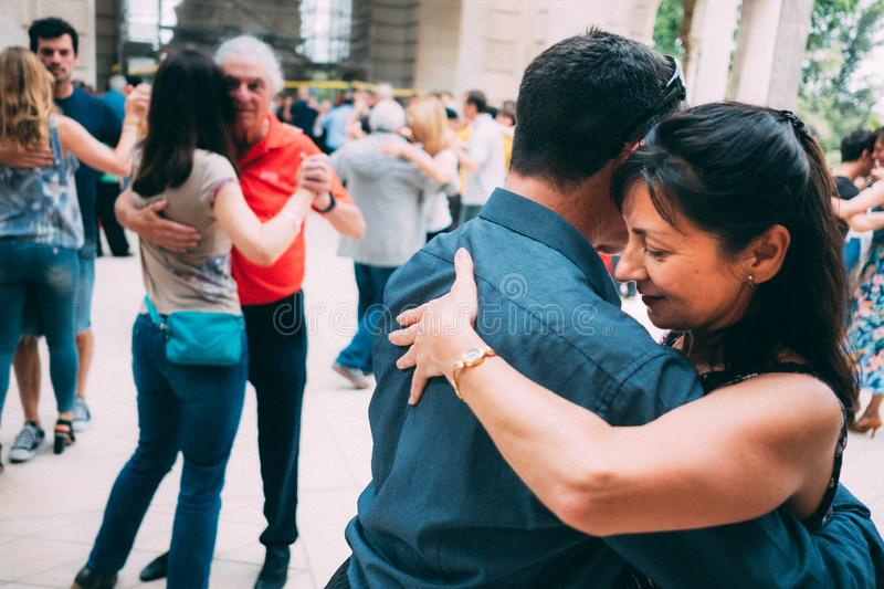 Barcelona, Spain - 10 july 2019: adult couple dancing tango with passion and huggin tight in outdoors park moving close to each royalty free stock photos