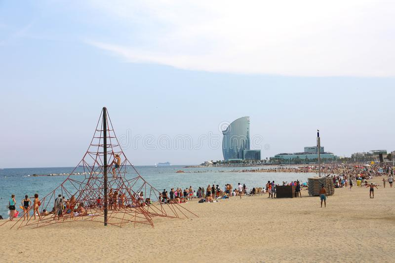 BARCELONA, SPAIN - JULY 11, 2018: amazing view of Barceloneta be. Ach with people enjoying sunny day in Barcelona and W hotel on background, Catalonia, Spain royalty free stock photo