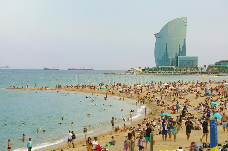 BARCELONA, SPAIN - JULY 11, 2018: amazing view of Barceloneta beach with people enjoying a sunny day Barcelona and W hotel. On a background, Catalonia, Spain royalty free stock images