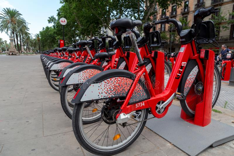 Red bicycles available for rent parked in a row at Passeig de Lluis Companys. Concept of environmentally sustainable transport. Barcelona, Spain - July 9, 2019 royalty free stock image