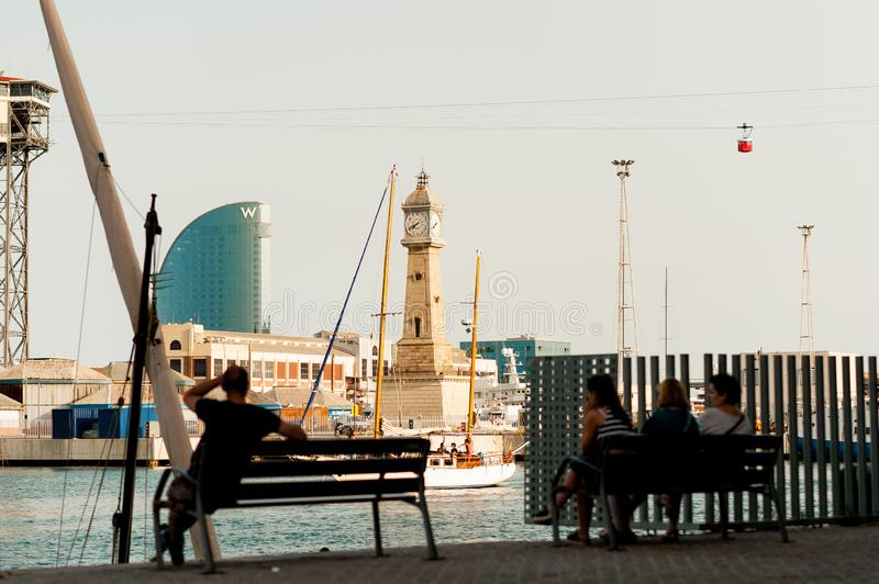 Barcelona, Spain - 7 july 2019: tourists relax on benches looking at port vell harbour with w hotel, cableway and historic tower. Clock at sunset stock photo