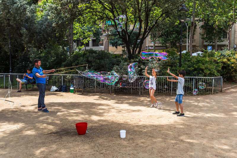 BARCELONA, SPAIN. 6 July 2017: Unidentified children play in Gaudi Square with soap bubbles made by a street artist stock image
