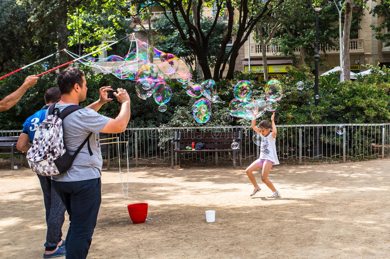 BARCELONA, SPAIN. 6 July 2017: Unidentified tourist takes photos of children playing with soap bubbles made by street artists in Gaudi Square stock photos