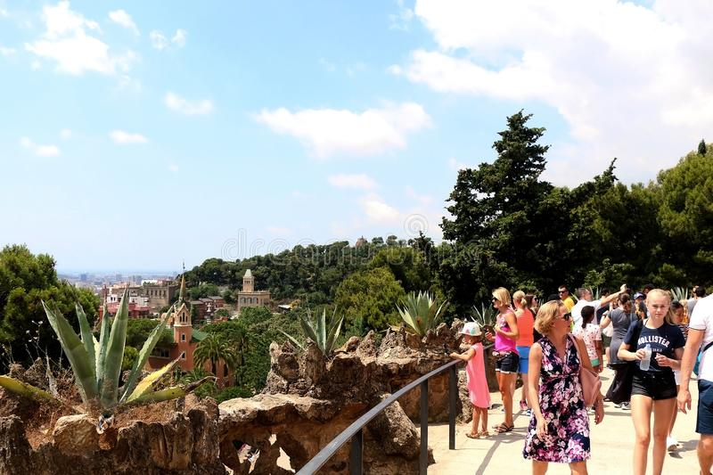 Barcelona, Spain. July 6, 2018: Visitors enjoying sunny summer day in Park Güell, . Aerial view of Barcelona in the background royalty free stock images