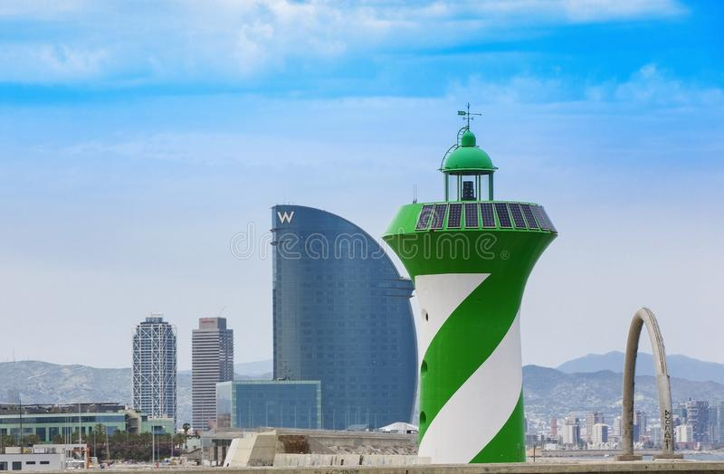 Hotel W, designed by architect Ricardo Bofill, Barcelona port and green lighthouse of Barcelona. Barcelona, Spain - June 17, 2018: Hotel W, designed by royalty free stock photos