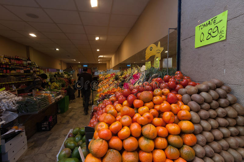Barcelona, Spain, March 2016: Countertop grocery store with fresh fruit racks. On front royalty free stock photos