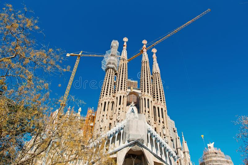 Barcelona, Spain - March 30, 2016: Sagrada familia and cranes on blue sky. Basilica and expiatory church of Holy Family. Roman catholic. Gaudi design royalty free stock photography