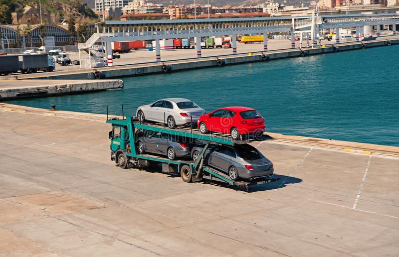 Barcelona, Spain - March 30, 2016: tow truck carry Seat and Mercedes cars in sea port. Auto export and import trade royalty free stock photos