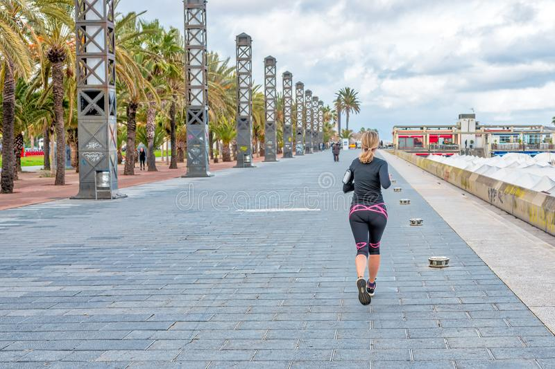 BARCELONA, SPAIN - MARCH 13: Woman jogging in Barcelona near to the sea stock image