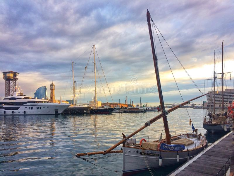 Barcelona, Spain, May 2018: Traditional mediterranean boat and super yachtin harbour of Barcelona. Barcelona, Spain, May 2018: Traditional mediterranean boat and royalty free stock photography