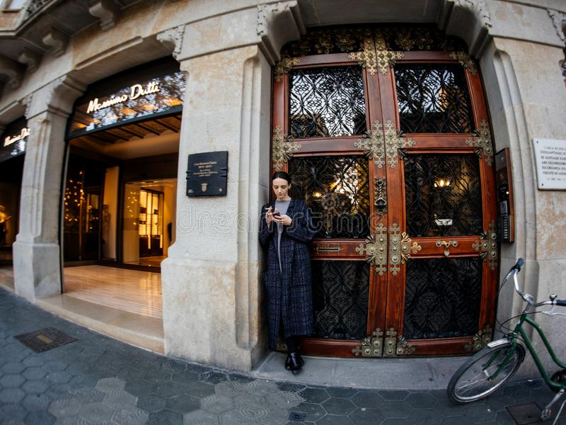 Young stylish woman smoking and using the mobile phone smartphone near the entrance of the luxury Massimo Dutti. Barcelona, Spain - Nov 13, 2017: young stylish royalty free stock image