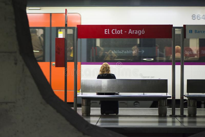 A woman sitting on a bench, in train station in the city. BARCELONA, SPAIN - NOVEMBER 6, 2015: A woman sitting on a bench, awaits the arrival of a commuter stock photography