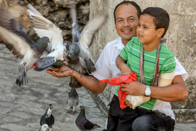 Barcelona / Spain - Oct./2018: Adult latin man with a boy on knees feeds the pigeons on the city street. Happy life, family values royalty free stock image