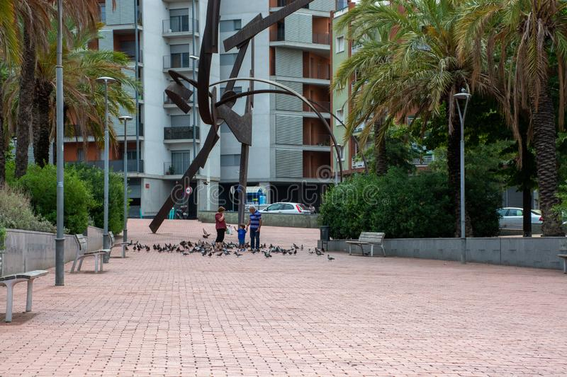 Family playing and feeding pidgeons next to sculpture in Barcelona. Barcelona, Spain - 26th July 2017 - Family playing and feeding pidgeons next to sculpture on stock photography