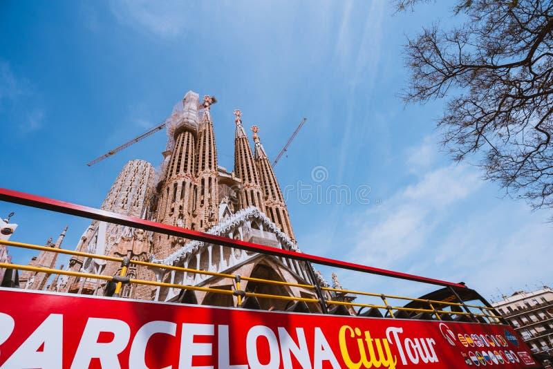 BARCELONA, SPANIEN - 25. April 2018: Touristischer Bus Barcelona-Stadtrundfahrt vor berühmter Basilika Sagrada Familia dennoch ni lizenzfreie stockfotos