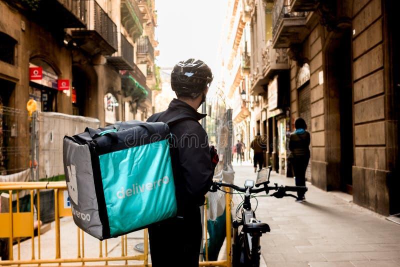 Barcelona, Spanien - 11. Dezember 2018: junges Deliveroo-delivey Dienstleistungsunternehmen durch Fahrrad in den Straßen der Stad lizenzfreie stockfotografie